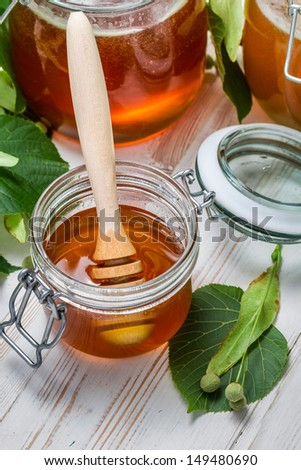 Closeup of honey in a jar and lime leaves - stock photo