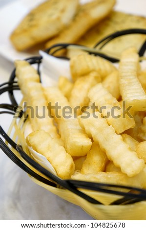 Closeup of hot Golden French Fries on wooden serving plate. (shallow depth of field) - stock photo