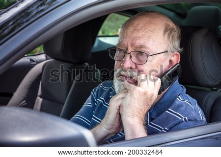 Closeup of hot, sweaty, frightened senior man in car calling for roadside assistance from his car phone - stock photo