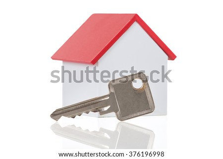 Closeup of house model and key on white background