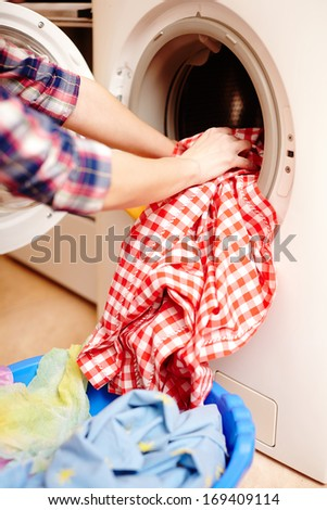 Closeup of housewife's hands putting the laundry into the washing machine - stock photo