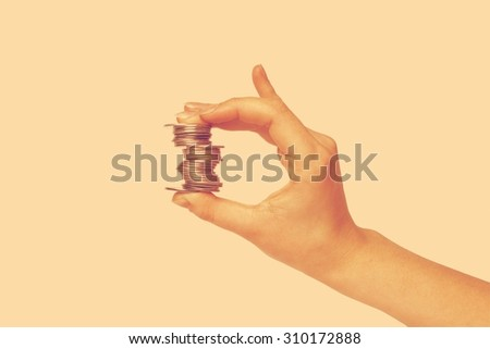 Closeup of human hand holding coins isolated on white