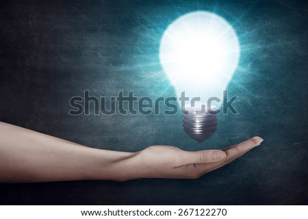 Closeup of human hand holding light bulb. Creativity concept  - stock photo