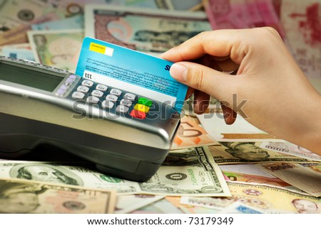 Closeup of human hand putting credit card into payment machine - stock photo