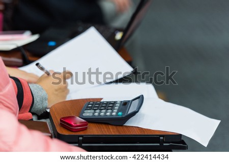 Closeup of human hand writing at a conference. - stock photo