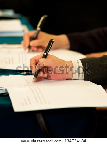 Closeup of human hand writing on a paper. - stock photo