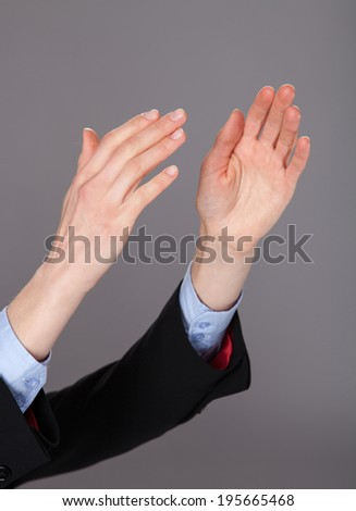 Closeup of human hands applauding on gray background