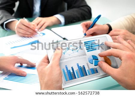 Closeup of human hands  over business documents at meeting - stock photo