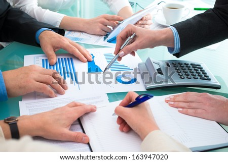 Closeup of human hands  over business documents at meeting