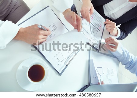 Closeup of human hands working with documents and analyzing business