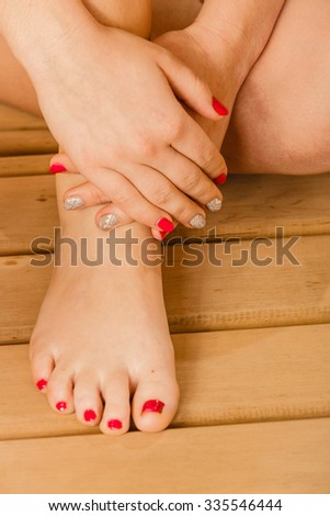 Closeup of human woman legs feet, hands with sauna bucket and ladle. Person relaxing resting in spa.