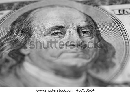 Closeup of hundred dollar bill isolated on white background with frown on face - stock photo