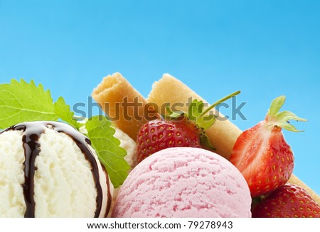 closeup of ice cream scoops with strawberries, waffles and chocolate topping against vibrant blue background, copy space in upper half - stock photo