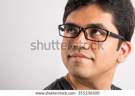 closeup of indian man with glasses, smiling asian man wearing glasses, Closeup portrait of young indian man in glasses, portrait of a handsome indian happy man, asian happy man looking upward