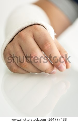 Closeup of injured male hand in plaster. - stock photo
