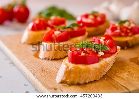 Closeup of Italian bruschetta with tomato, basil and garlic on a chopping board