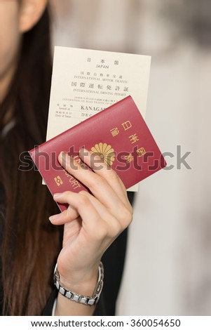Closeup of Japanese passport and international drivers license holding by Japanese business woman.