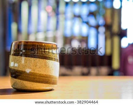 Closeup of Japanese tea cup pottery over restaurant blurred background / interior still life