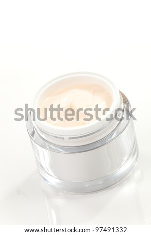 Closeup of jar of moisturizing face cream surrounded by pink tulip flowers - stock photo