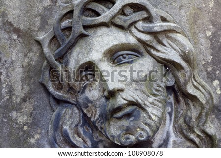 Closeup of Jesus Christ on old grunge grave - stock photo