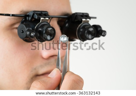 Closeup of jeweler examining diamond with magnifying loupe against white background