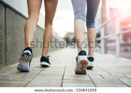 Closeup of joggers' feet and shoes while in motion - stock photo