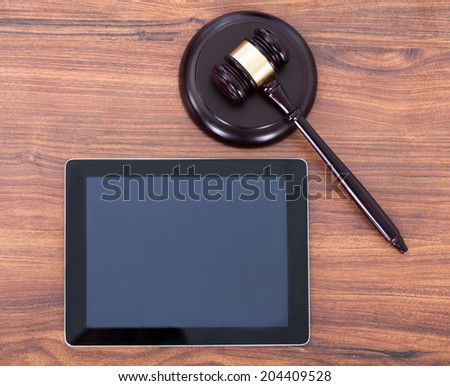 Closeup of judge mallet on block by digital tablet in courtroom - stock photo