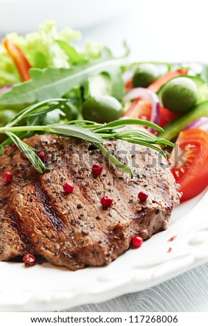 Closeup of juicy grilled beef steak with salad. Concept for healthy nutrition.
