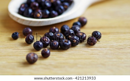 Closeup of juniper berry organic spices in wood spoon on a wooden background. Aroma herbs for healthy food.