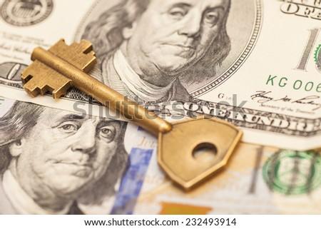 Closeup of  key on hundred dollar bills  - stock photo