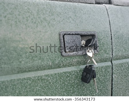 Closeup of keys in a lock of frozen car door, selective focus shot
