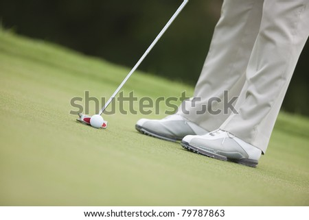 Closeup of knee-down shot of golfer about to putt the ball.