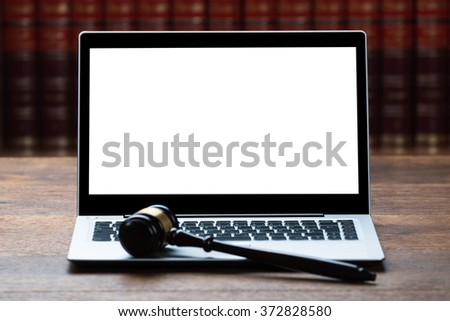 Closeup of laptop and mallet on table in courtroom - stock photo