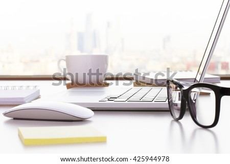 Closeup of laptop, glasses, coffee cup and other items on white desktop with blurry city in the background - stock photo