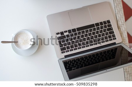 Closeup of laptop next to coffee in the cup