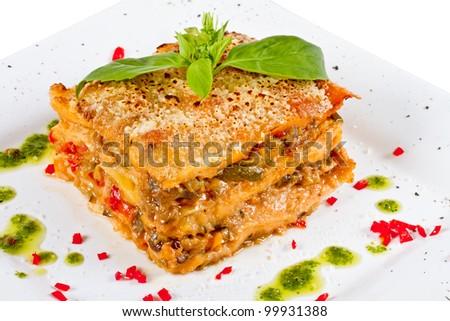 Closeup of lasagna and basil fork - stock photo