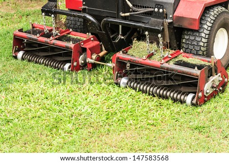 Closeup of lawn mower on green grasses field