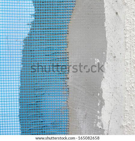Closeup of layers over styrofoam insulation, mesh, plaster, cement, mortar - stock photo