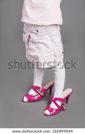 Closeup of Legs of Little Girl Trying On Mother's Unsuitable High Heel Shoes. Over Gray Background.Vertical Image - stock photo