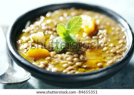 closeup of lentil soup, the lentils have cooked for 3 hours in order to form its own thick sauce, it also has carrots and onions - stock photo
