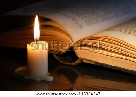 Closeup of lighting candle near open old book