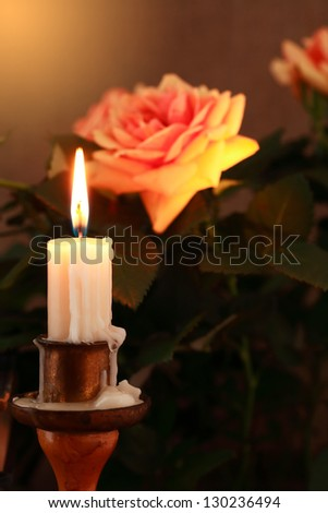 Closeup of lighting candle on dark background with beautiful rose - stock photo