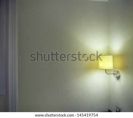 Closeup of lit sconce shining light onto corner wall in the room - stock photo