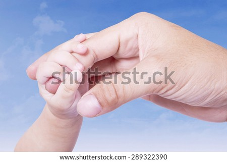 Closeup of little baby hand holding a finger of father's hand under blue sky - stock photo