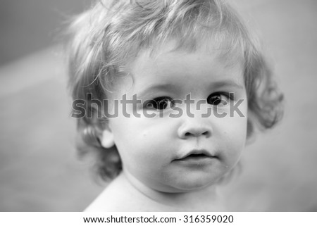 Closeup of little beautiful joyful playful baby boy with blonde curly hair round cheeks kind eyes looking forward outdoor black and white, horizontal picture - stock photo