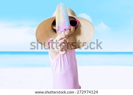 Closeup of little child with a big hat standing on the beach while wearing swimwear and showing ice cream - stock photo