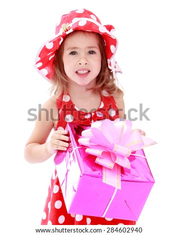 Closeup of little girl in a red polka dot dress holds up a box with a gift- isolated on white background - stock photo