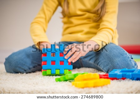 Closeup of little girl in yellow pullover holding lego fragments. - stock photo