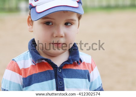 Closeup of little handsome boy in cap outdoor at summer, shallow dof - stock photo