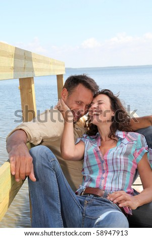 Closeup of loving couple sitting on a pontoon by a lake